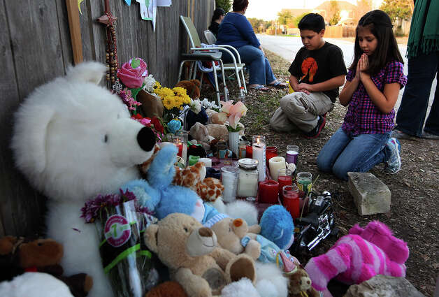 Briana Linstad, 7, and her 10-year-old brother, Ricky, pray at a memorial erected for Brandon Abrams on the Northwest Side of the city. Photo: Kin Man Hui, San Antonio Express-News / © 2012 San Antonio Express-News