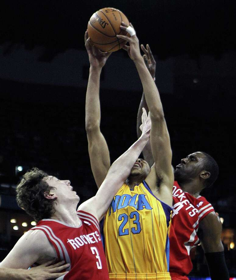 Omer Asik, left, and Patrick Patterson, right, make rebounding a tough proposition for the Hornets' Anthony Davis. The Rockets outrebounded their counterparts 44-34 in cruising to victory Friday night in New Orleans. Photo: Gerald Herbert, STF / AP