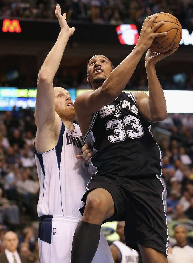 DALLAS, TX - JANUARY 25:  Boris Diaw #33 of the San Antonio Spurs takes a shot against Chris Kaman #35 of the Dallas Mavericks at American Airlines Center on January 25, 2013 in Dallas, Texas.  NOTE TO USER: User expressly acknowledges and agrees that, by downloading and or using this photograph, User is consenting to the terms and conditions of the Getty Images License Agreement. Photo: Ronald Martinez, Getty Images / 2013 Getty Images