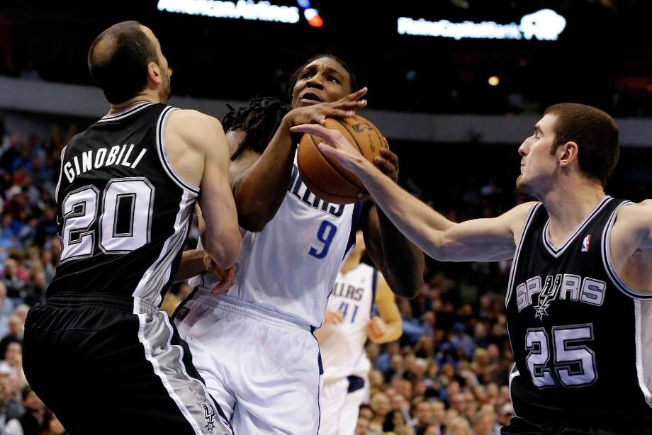 San Antonio Spurs' Manu Ginobili (20), of Argentina, and Nando de Colo (25), of France, stop a drive to the basket by Dallas Mavericks' Jae Crowder (9) in the first half of an NBA basketball game on Friday, Jan. 25, 2013, in Dallas. (AP Photo/Tony Gutierrez) Photo: Tony Gutierrez, Associated Press / AP