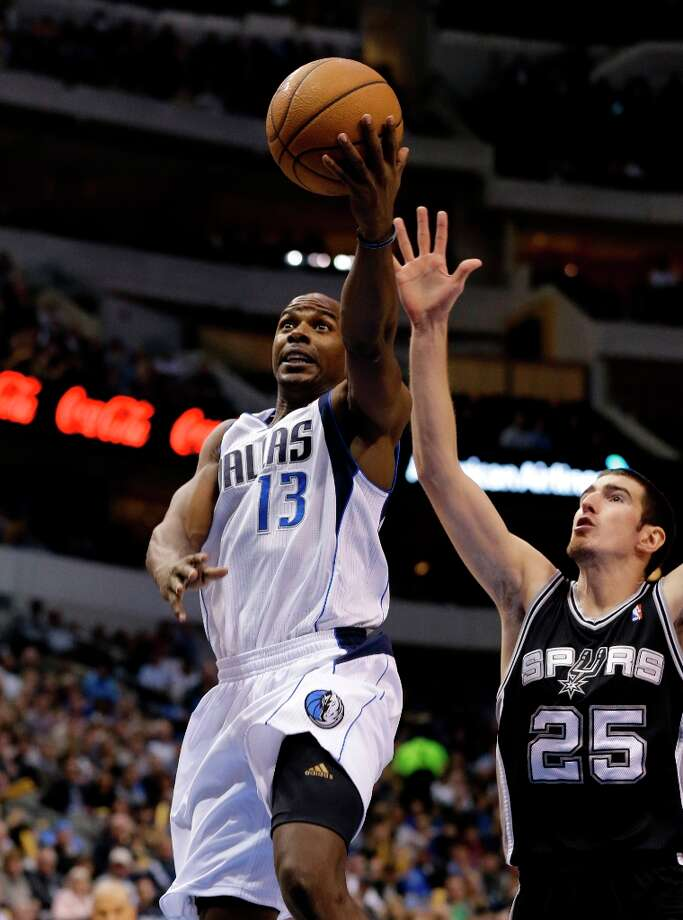 Dallas Mavericks' Mike James (13) goes up for a shot as San Antonio Spurs' Nando de Colo (25) of France defends in the first half of an NBA basketball game Friday, Jan. 25, 2013, in Dallas. (AP Photo/Tony Gutierrez) Photo: Tony Gutierrez, Associated Press / AP