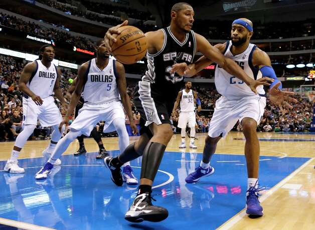 San Antonio Spurs' Boris Diaw (33) of France attempts to get through the defense of Dallas Mavericks' Jae Crowder (9), Bernard James (5) and Vince Carter (25) in the second half of an NBA basketball game Friday, Jan. 25, 2013, in Dallas. The Spurs won 113-107. (AP Photo/Tony Gutierrez) Photo: Tony Gutierrez, Associated Press / AP