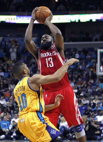 Rockets guard James Harden shoots over Hornets guard Eric Gordon. Photo: Gerald Herbert