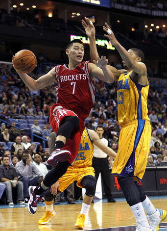 Rockets point guard Jeremy Lin looks to pass the ball while in midair. Photo: Gerald Herbert