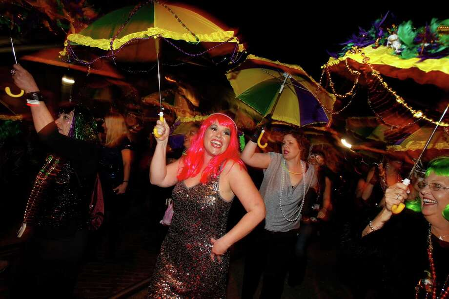 Galvestonian Amy Canaba, center, and friends brought some spunk to the first Funky Uptown Umbrella Brigade Parade in 2011. Photo: Melissa Phillip, Staff / Houston Chronicle