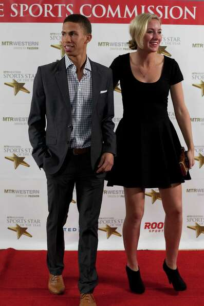 UW cross county and track athlete Katie Flood, right, pauses on the red carpet with Michael Miller d