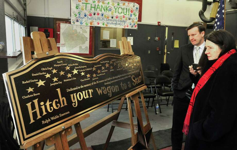 U.S. Sen. Chris Murphy and Mary D'Avino look at look at the bronze plaque after thestar and plaque dedication ceremony at the Sandy Hook Volunteer Fire & Rescue Company Saturday, Jan. 26, 2013. D'Avino's daughter, Rachel, is one of the victims the stars represent. Photo: Michael Duffy / The News-Times