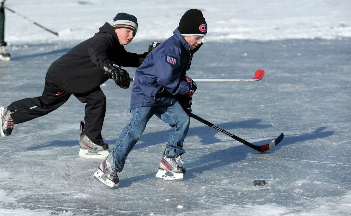 David Pozma, left, and Will Lodge, right, both 9, play ice hockey on Gorham's Pond in Darien on Saturday, January 27, 2013.