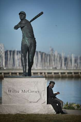 Robert Jenkins reads a book beneath a statue of Willie McCovey in China Basin Park across from AT&T park on Friday, January 25, 2013 in San Francisco, Calif. Photo: Lea Suzuki, The Chronicle