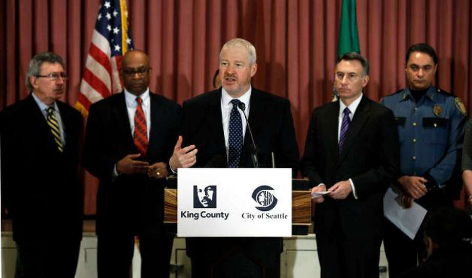 Seattle Mayor Mike McGinn, center, speaks Jan. 8, at a news conference announcing the gun buyback program. Behind him, from left, are former Seattle mayors Charles Royer, and Norm Rice, King Co. Executive Dow Constantine, and Seattle Deputy Police Chief Nick Metz. (Ted Warren/AP)