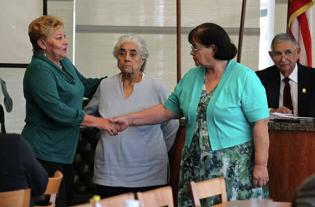 Maria Vasquez (right), mother of Anna Vasquez, shakes hands with Gloria Herrera (left), mother of Elizabeth Ramirez, as Anna Vasquez's aunt, Valeria Pachecano stands in between during a meeting of the San Antonio Crime Coalition on Saturday, Jan. 26, 2013. Anna Vasquez could not attend the meeting because of her parole restrictions. Vazquez along with three other women are fighting for exoneration from a 1994 sexual assualt case. Anna Vasquez served more than a decade of time in jail while the three other women are still serving time. Photo: Bob Owen, San Antonio Express-News / © 2012 San Antonio Express-News
