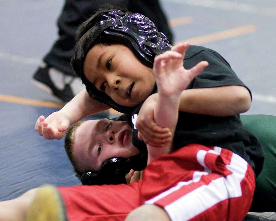 Jayson You, top, of Stadley Rough, Danbury, won the Western Connecticut Elementary League Championship title in the 2d and 3d grade #8 weight division with a victory over Brendan Mulvihill of the New Milford Wrestling Associate Saturday at the Danbury PAL Center. Photo: Barry Horn