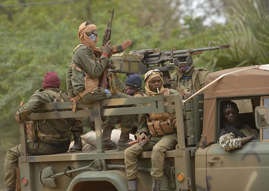 "Malian soldiers patrol aboard a vehicule mounted with a machine gun in a street of Diabaly (400km north of the capital Bamako) on January 26, 2013. French-led Malian troops recaptured the Islamist stronghold of Gao, today, the biggest town in northern Mali, and troops from Niger and Chad ""will now take up the baton,"" the French defence ministry said. AFP PHOTO / ERIC FEFERBERGERIC FEFERBERG/AFP/Getty Images Photo: Eric Feferberg, AFP/Getty Images"