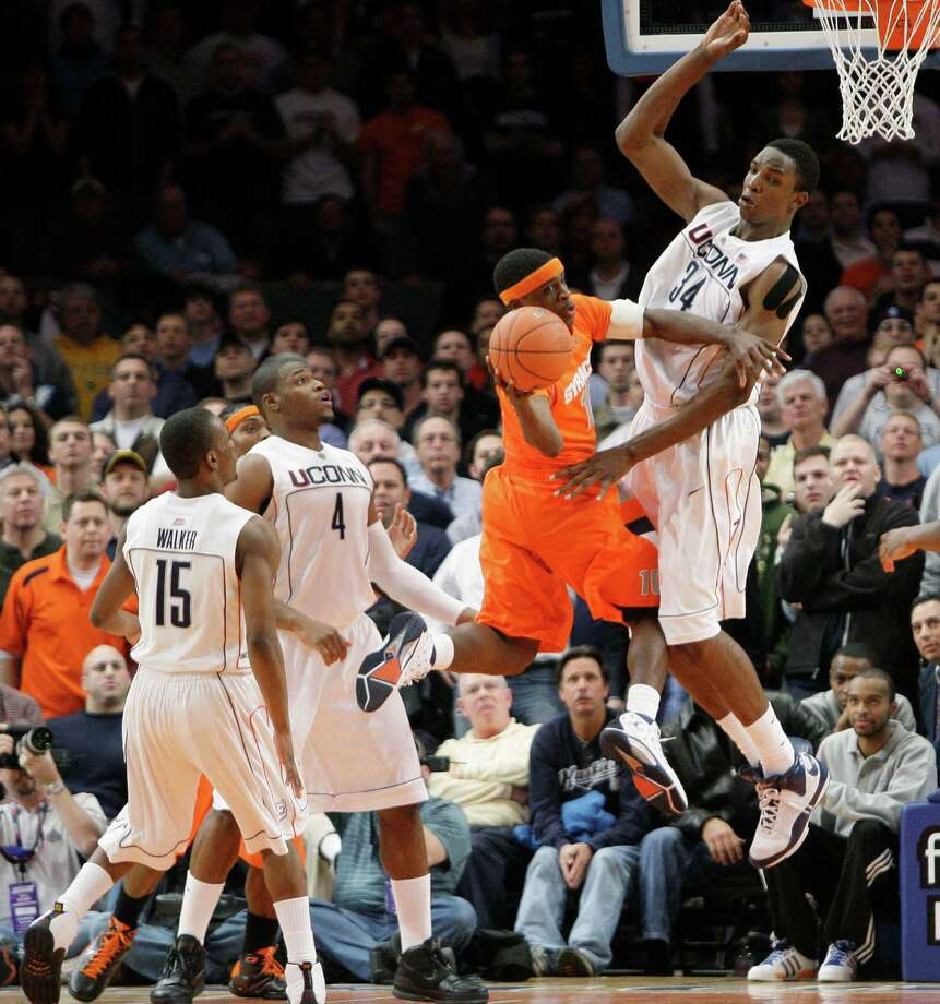Syracuse's Jonny Flynn, center, passes the ball off against Connecticut's Hasheem Thabeet, right, late in the second half of a quarterfinal NCAA college basketball game at the Big East men's tournament Thursday, March 12, 2009 at Madison Square Garden in New York. Syracuse won 127-117 in six overtimes. (AP Photo/Julie Jacobson) Photo: Julie Jacobson, ASSOCIATED PRESS / AP2009