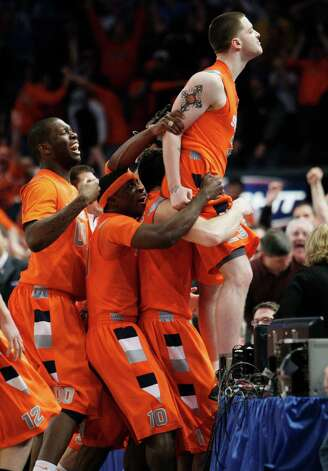Syracuse's Eric Devendorf is mobbed by teammates as he stands on a table after making a three-point basket at the end of regulation against Connecticut during a quarterfinal NCAA college basketball game at the Big East men's tournament Thursday, March 12, 2009 at Madison Square Garden in New York. The shot, which would have won the game and was originally ruled good, was reviewed and referees determined the clock had run down before the ball left Devendorf's hand. The game extended into six overtime periods before Syracuse won 127-117. (AP Photo/Julie Jacobson) Photo: Julie Jacobson, ASSOCIATED PRESS / AP2009