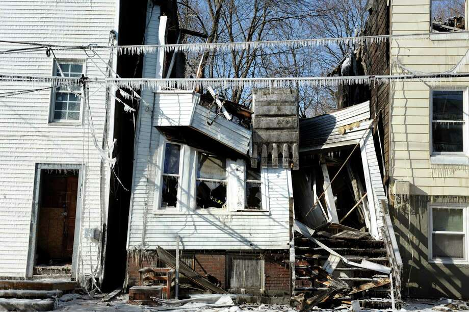 A backhoe pulls down the first of three fire-damaged houses on Dove Street on Saturday, Jan. 26, 2013, in Albany, N.Y. (Cindy Schultz / Times Union) Photo: Cindy Schultz