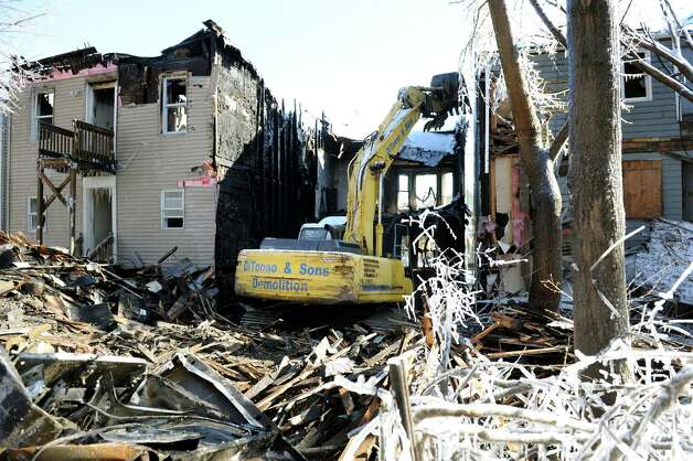 From the backyard, a backhoe pulls down the first of three fire-damaged houses on Dove Street on Saturday, Jan. 26, 2013, in Albany, N.Y. (Cindy Schultz / Times Union) Photo: Cindy Schultz