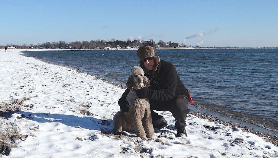 Paul Berg and his dog Rosie enjoy a brisk walk along snow-covered Penfield Beach on Saturday morning.  FAIRFIELD CITIZEN, CT 1/26/13 Photo: Mike Lauterborn / Fairfield Citizen contributed