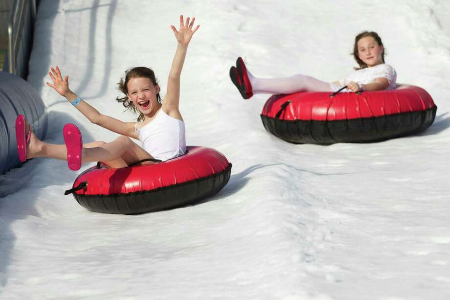 Grace Elacquala laughs as she slides down a snow hill during Winterfest at the Pearland Recreation Center and Natatorium Saturday, Jan. 26, 2013, in Pearland. Photo: Brett Coomer, Houston Chronicle / © 2013 Houston Chronicle