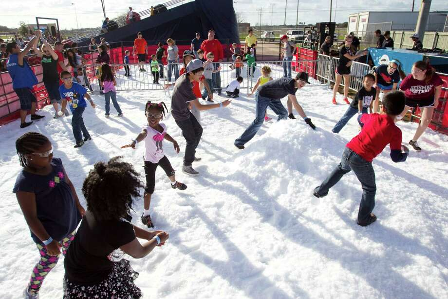 Children take to the man-made snow for a snowball fight during Winterfest at the Pearland Recreation Center and Natatorium Saturday, Jan. 26, 2013, in Pearland. Photo: Brett Coomer, Houston Chronicle / © 2013 Houston Chronicle