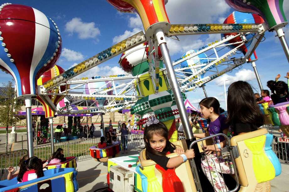 Children and adults take a spin on a carnival ride during Winterfest at the Pearland Recreation Center and Natatorium Saturday, Jan. 26, 2013, in Pearland. Photo: Brett Coomer, Houston Chronicle / © 2013 Houston Chronicle