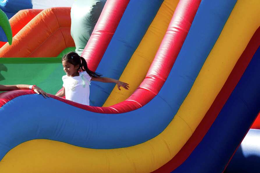 Dasia Ram smiles as she emerges from a blow-up rainbow colored slide during Winterfest at the Pearla