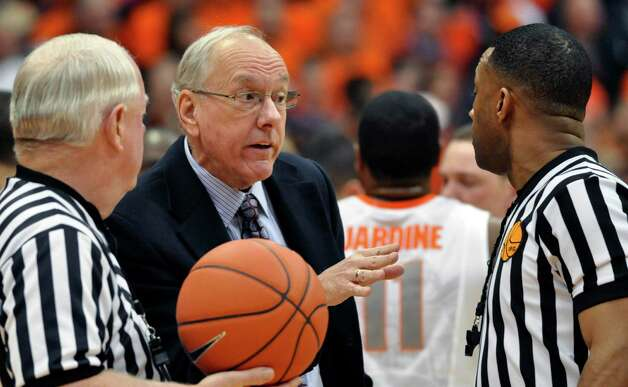 Syracuse head coach Jim Boeheim talks with officials Jeff Anderson, right, and Tim Higgins during the first half against Connecticut in an NCAA college basketball game in Syracuse, N.Y., Saturday, Feb. 11, 2012. Syracuse won 85-67. (AP Photo/Kevin Rivoli) Photo: Kevin Rivoli, Associated Press / FR60349 AP