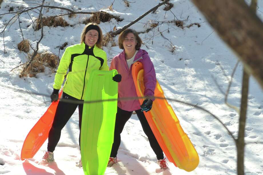 Pam Skripak and Julia Richards take a few sleds to take advantage of the last snow and sun on an awesome hidden hillside in Bethlehem along side the Normanside Creek. (Dave Gordon)