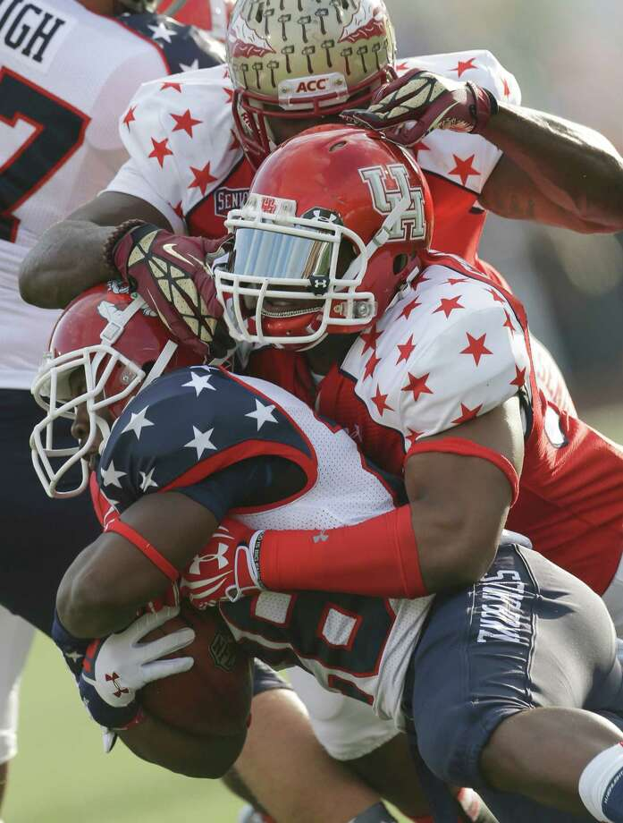 Senior Bowl North Squad running back Robbie Rouse of Fresno State (28) is stopped by South Squad linebacker Phillip Steward of Houston and Vince Williams, top, of Florida State in the first half of the Senior Bowl college football game at Ladd-Peebles Stadium in Mobile, Ala., Saturday, Jan. 26, 2013. (AP Photo/Dave Martin) Photo: Dave Martin, Associated Press / AP