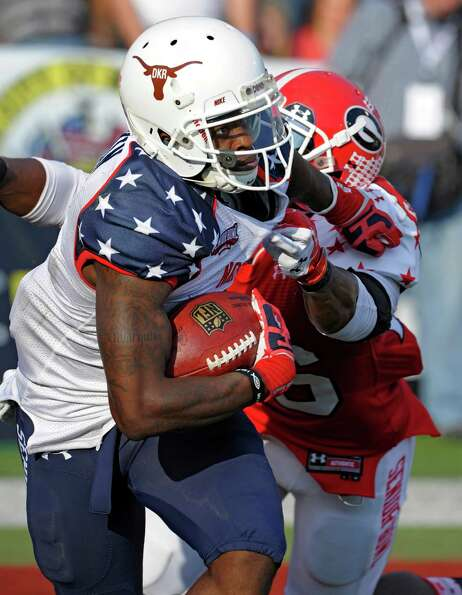 North Squad wide receiver Marquise Goodwin, front, of Texas,  pulls away from South Squad defensive