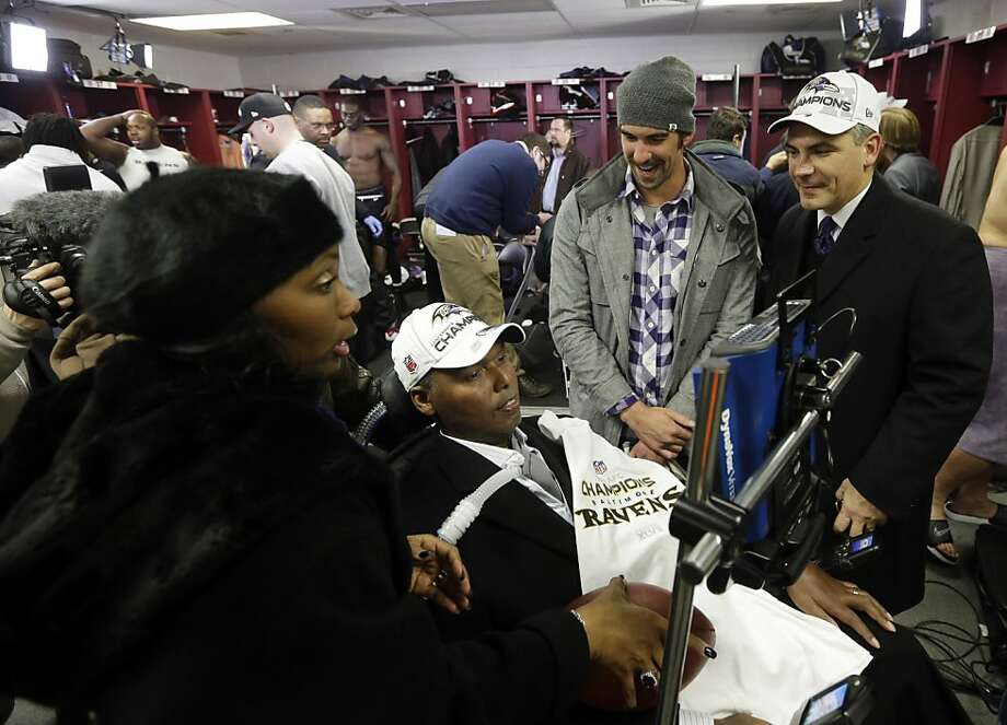 ALS patient O.J. Brigance joins Ravens' celebration with his wife and Michael Phelps (in gray cap). Photo: Elise Amendola, Associated Press