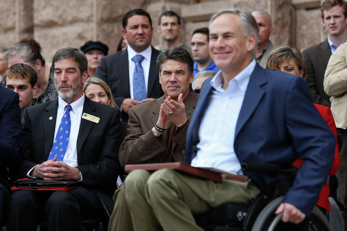 Governor Rick Perry applauds for Attorney General Greg Abbott, right, as Abbott goes to the podium to introduce Perry during the Texas Alliance for Life Rally at the Texas State Capitol in Austin on Saturday, Jan. 26, 2013. At left, is Joseph Pojman, Executive Director, Texas Alliance For Life.