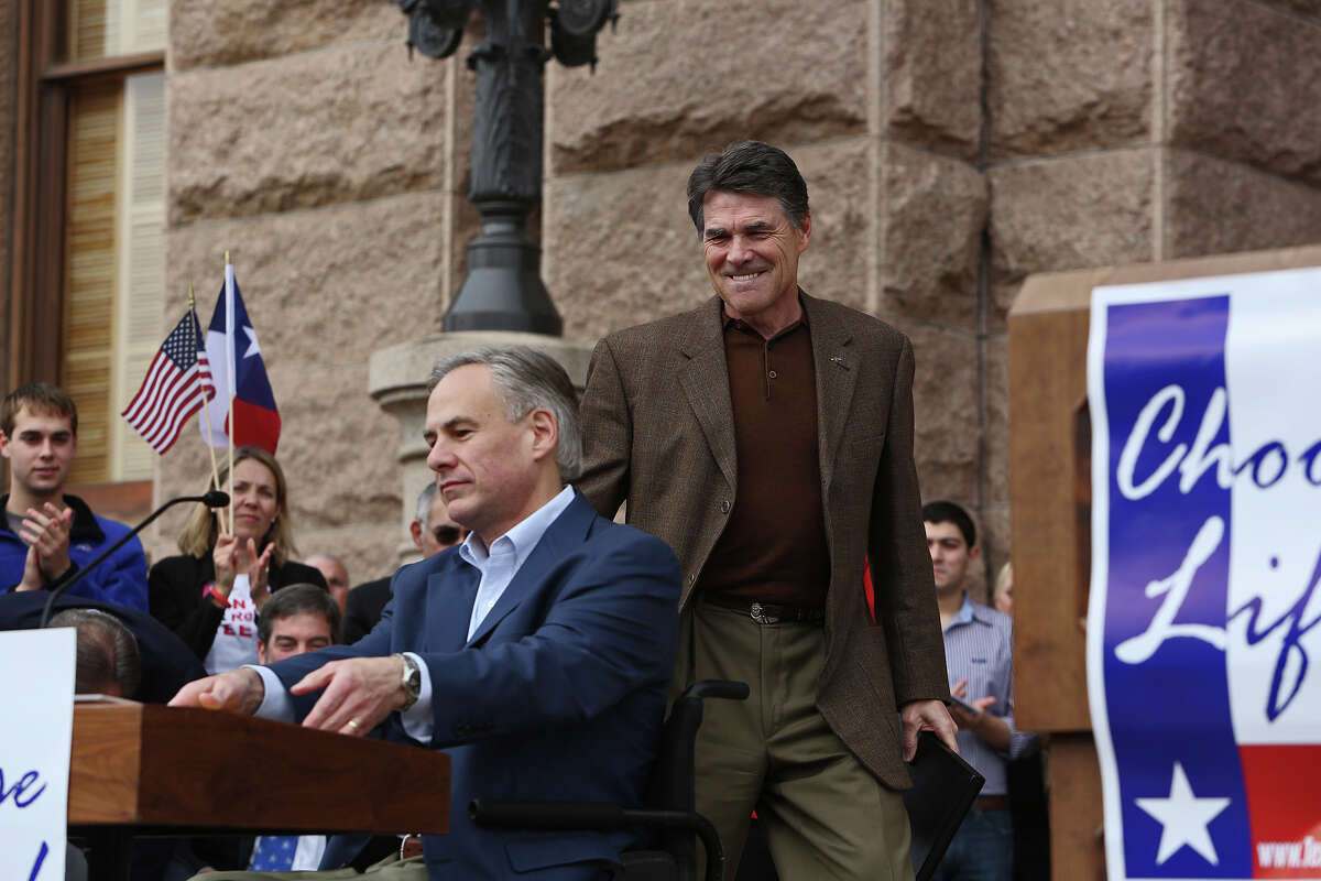 Governor Rick Perry, center, approaches Attorney General Greg Abbott after Abbott, left, introduced Perry during the Texas Alliance for Life Rally at the Texas State Capitol in Austin on Saturday, Jan. 26, 2013.