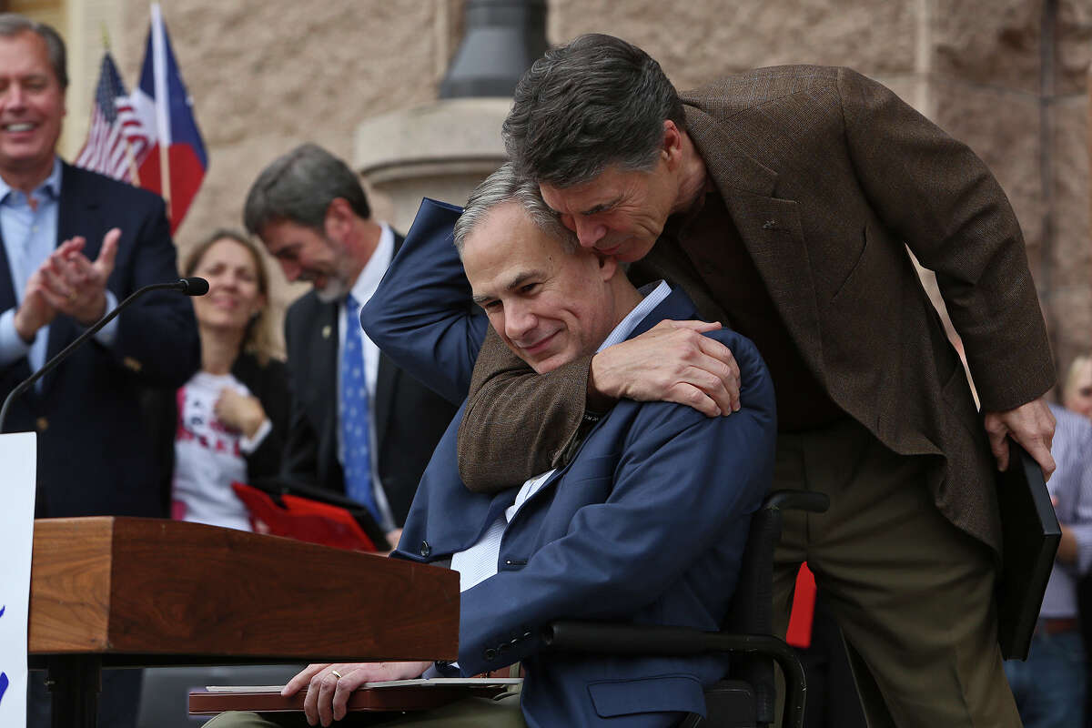 Governor Rick Perry, right, hugs Attorney General Greg Abbott after Abbott introduced Perry during the Texas Alliance for Life Rally at the Texas State Capitol in Austin on Saturday, Jan. 26, 2013.