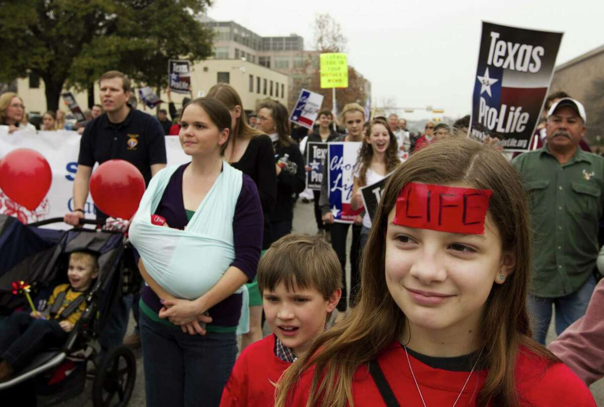 Robin Newberry, 12, of Houston, marches during the Rally for Life at the Capitol, Saturday, Jan. 26, 2013 in Austin, Texas, An estimated 3,000 people have marched on the state Capitol for an anti-abortion rally to mark the 40th anniversary of the Supreme Court decision legalizing abortion. (AP Photo/Austin American-Statesman, Jay Janner) MAGS OUT; NO SALES; INTERNET AND TV MUST CREDIT PHOTOGRAPHER AND STATESMAN.COM