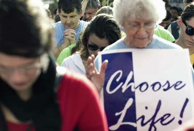 Daniel Spilde, of San Antonio, prays during the Rally for Life at the Capitol, Saturday, Jan. 26, 2013 in Austin, Texas, An estimated 3,000 people have marched on the state Capitol for an anti-abortion rally to mark the 40th anniversary of the Supreme Court decision legalizing abortion. (AP Photo/Austin American-Statesman, Jay Janner)  MAGS OUT; NO SALES; INTERNET AND TV MUST CREDIT PHOTOGRAPHER AND STATESMAN.COM Photo: Jay Janner, MBO / Austin American-Statesman