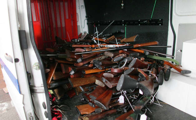 A pile of guns grows in a van as they are collected during the City of Seattle's gun buy back program on Saturday, January 26, 2013. The gun exchange program brought out people looking for deals on firearms. The program handed out $80,000 worth of gift cards in exchange for weapons brought in by the public. Photo: JOSHUA TRUJILLO, SEATTLEPI.COM / SEATTLEPI.COM