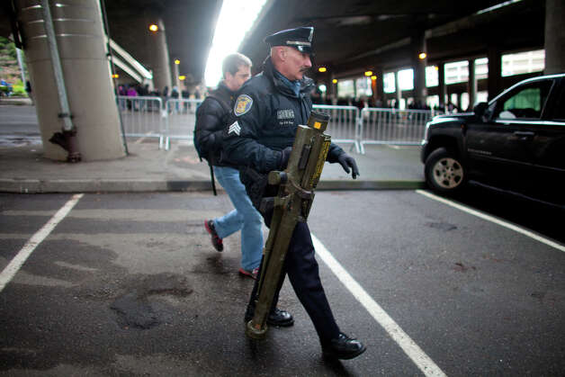 Seattle Police Department Seattle Police Sgt. Paul Gracy carries an inert surface to air missile launcher brought to the City of Seattle's gun buy back program on Saturday, January 26, 2013. The surface to air launcher was brought to the buyback and then purchased from a person in line for $100 by another citizen. Police took the already used, single use weapon until they could determine if it was safe and if the man could have it back. Photo: JOSHUA TRUJILLO, SEATTLEPI.COM / SEATTLEPI.COM