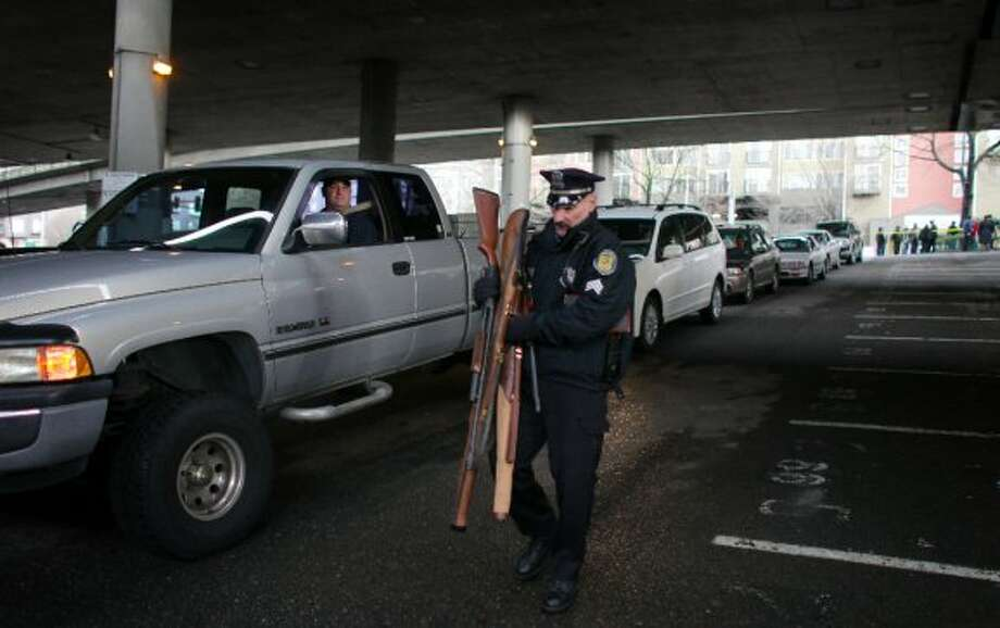Seattle Police Sgt. Paul Gracy carries weapons turned in during the City of Seattle's gun buy back program on Saturday, January 26, 2013. The program handed out $80,000 worth of gift cards in exchange for weapons brought in by the public.