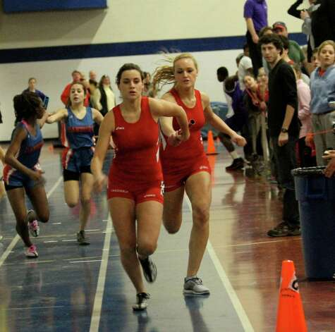 Greenwich's Emily Johnson, rear, passes the baton to Naomi Leeds in the 4x200 relay at the FCIAC West Division championships at Staples in Westport, Saturday. Photo: Isabel Leeds/Contributed Photo
