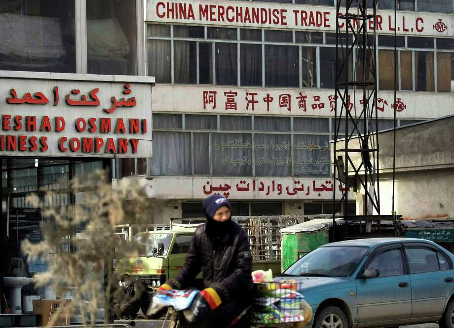 In this Tuesday, Jan. 22, 2013 photo, an Afghan man rides his bike past a China Merchandise Trade Center in Kabul, Afghanistan. China, long a bystander to the bloody conflict in neighboring Afghanistan, is accelerating its involvement as U.S.-led forces prepare to withdraw, attracted by its vast, untapped mineral resources and concerned that post-2014 chaos could fuel its own Islamist insurgents. (AP Photo/Musadeq Sadeq) Photo: Musadeq Sadeq