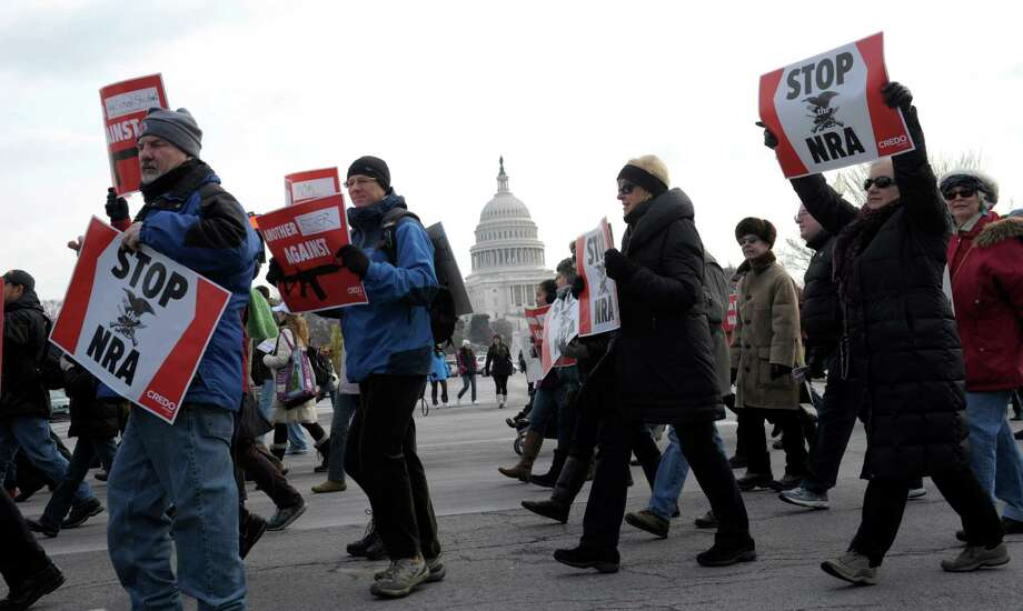 People walk from the U.S. Capitol to the Washington Monument in Washington, Saturday, Jan. 26, 2013, during a march on Washington for gun control. (AP Photo/Susan Walsh) Photo: Susan Walsh