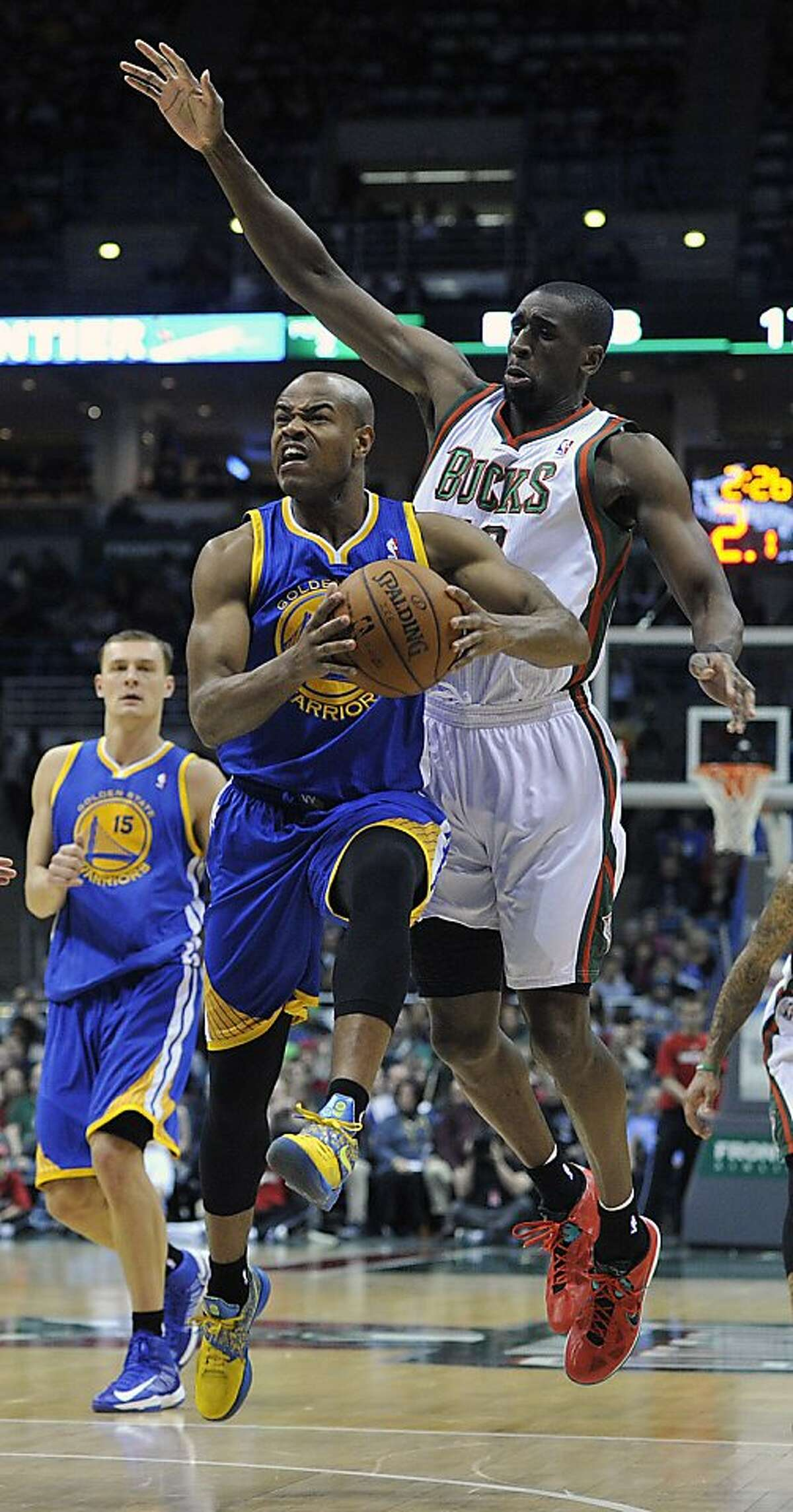 Golden State Warriors' Jarrett Jack, front left, drives to the basket around Milwaukee Bucks' Ekpe Udoh during the first half of an NBA basketball game on Saturday, Jan. 26, 2013, in Milwaukee. (AP Photo/Jim Prisching)