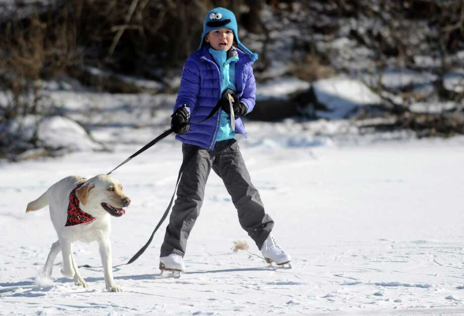 Mimi Sue Novak, 8, gets a pull from Millie as she skates on Gorham's Pond in Darien on Saturday, January 27, 2013. Photo: Lindsay Perry / Stamford Advocate