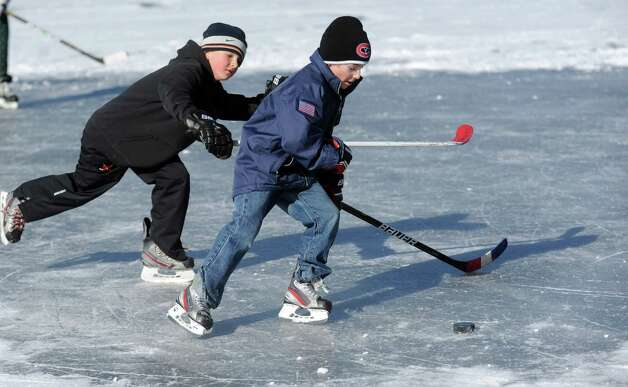 David Pozma, left, and Will Lodge, right, both 9, play ice hockey on Gorham's Pond in Darien on Saturday, January 27, 2013. Photo: Lindsay Perry / Stamford Advocate