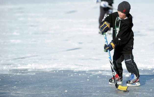 Mike Petersen, 9, plays ice hocket on Gorham's Pond in Darien on Saturday, January 27, 2013. Photo: Lindsay Perry / Stamford Advocate