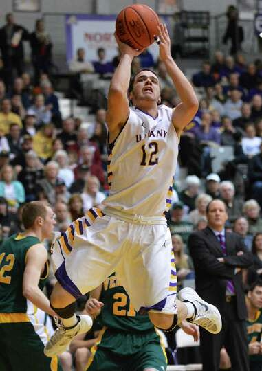 UAlbany's #12 Peter Hooley tries a jump shot against Vermont during an America East game at Sefcu Ar