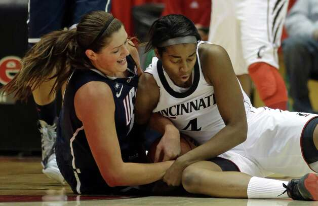 Cincinnati center Lesha Dunn (4) fights for a loose ball with Connecticut center Stefanie Dolson in the first half of an NCAA college basketball game on Saturday, Jan. 26, 2013, in Cincinnati. (AP Photo/Al Behrman) Photo: Al Behrman, Associated Press / AP