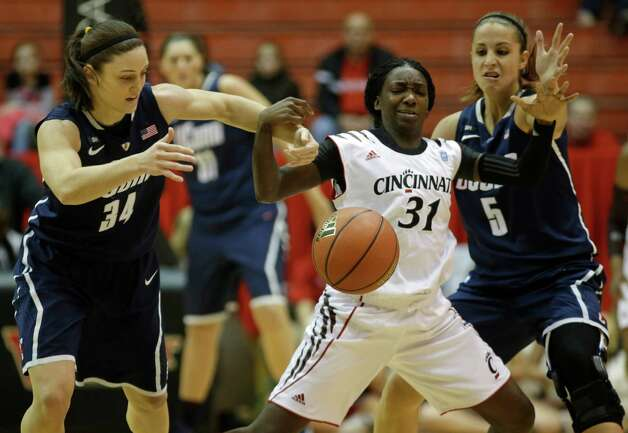 Cincinnati guard Dayeesha Hollins (31) has the ball knocked loose by Connecticut guard Kelly Faris (34) and guard Caroline Doty (5) in the first half of an NCAA college basketball game on Saturday, Jan. 26, 2013, in Cincinnati. (AP Photo/Al Behrman) Photo: Al Behrman, Associated Press / AP