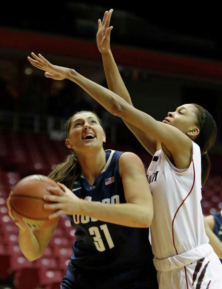 Connecticut center Stefanie Dolson (31) shoots against Cincinnati guard Alyesha Lovett in the first half of an NCAA college basketball game on Saturday, Jan. 26, 2013, in Cincinnati. (AP Photo/Al Behrman) Photo: Al Behrman, Associated Press / AP